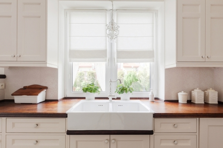 White, farmhouse sink in a wood kitchen countertop
