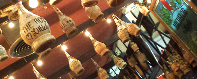 wine bottles hanging from rafters with lights - Filippe's Pizza, Restaurant Reviews, Recycle, Upcycle, Freecycle - Bill Salvatore, Arizona Elite Properties - Arizona Real Estate