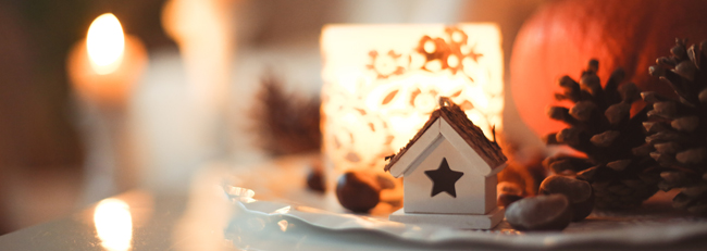 candles burning beside house shaped christmas orniments on a table - Holiday air quality, indoor air quality, toxic air, respatory illness, sweta-meininger_via Unsplash - Bill Salvatore, Arizona Elite Properties 602-999-0952 - Arizona Real Estate